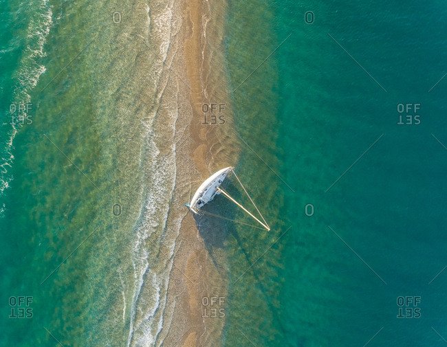 Aerial view of a small sailboat stranded in the Gulf of Patras, Greece.