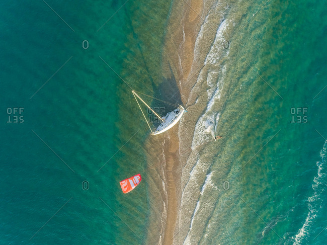 Aerial view of person kite surfing around stranded sailboat in the Gulf of Patras, Greece.