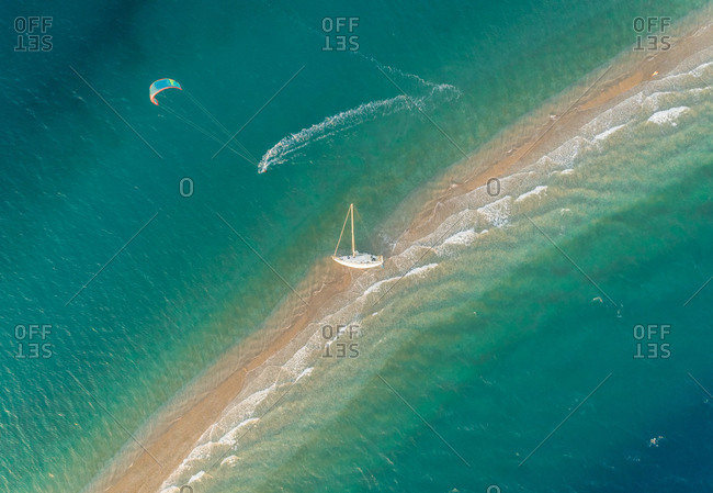 Aerial view of person kite surfing around stranded sailboat on sand bank in the Gulf of Patras, Greece.