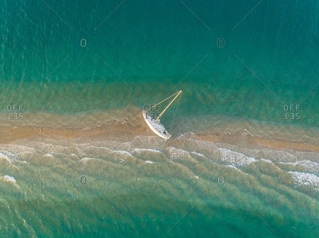 Aerial view of a small sailboat stranded on sand bank in the Gulf of Patras, Greece.
