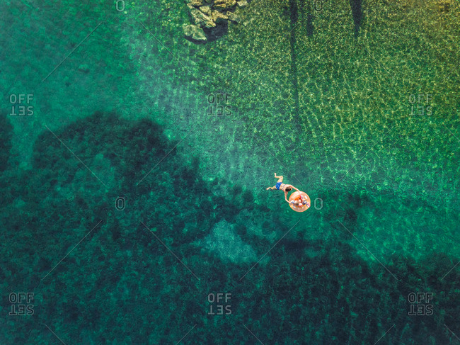 Aerial view of woman swimming with two kids on inflatable mattress on Trizonia island, Greece.