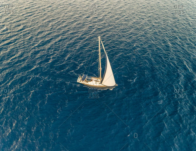 Aerial view of a sailboat sailing in the wind on the mediterranean sea, Vathi, Greece.