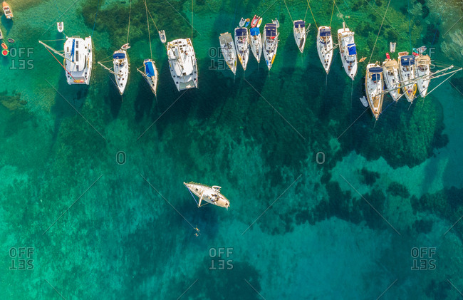 Aerial view of group of boats anchored in the mediterranean sea, Kastos island, Greece.