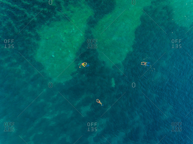 Aerial view of group swimming with flippers in the sea of Kioni island, Greece