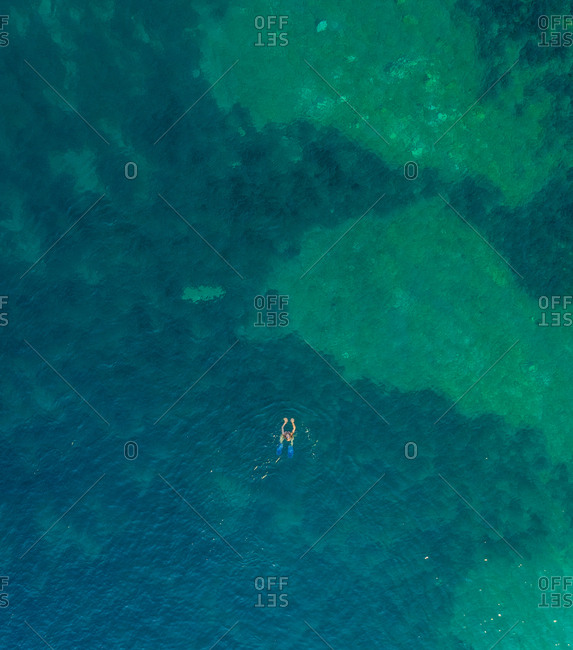 Aerial view of woman swimming with flippers in the sea of Kioni island, Greece