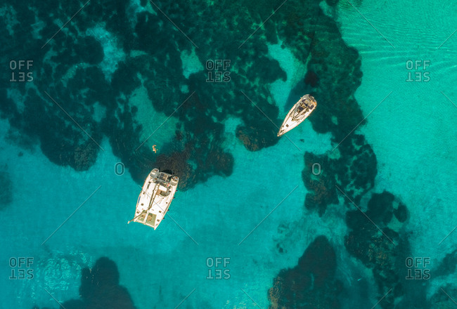 Aerial view of two sailboats anchored in the mediterranean sea with tourists swimming, next to Kastos island, Greece.