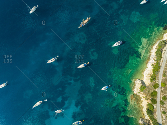 Aerial view of group of boats anchored in the mediterranean sea, next to Kastos island, Greece.