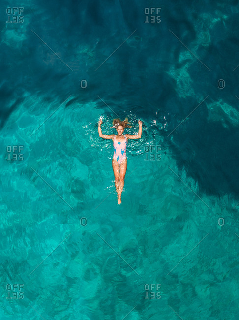 Aerial view of a woman floating in the sea of Atokos island, Greece