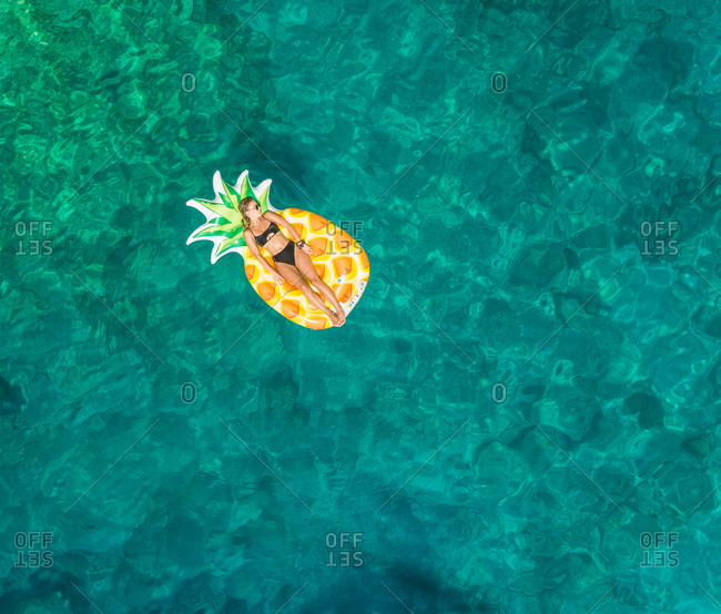 Aerial view of woman floating in inflatable pineapple on Atokos island, Greece.