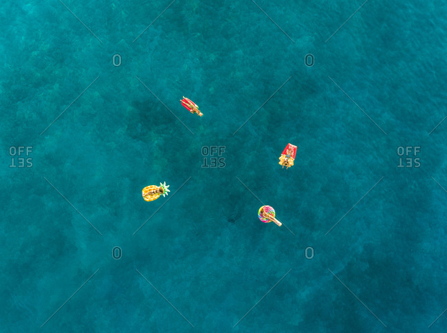 Aerial view of four friends floating on inflatable mattresses on Atokos island, Greece.