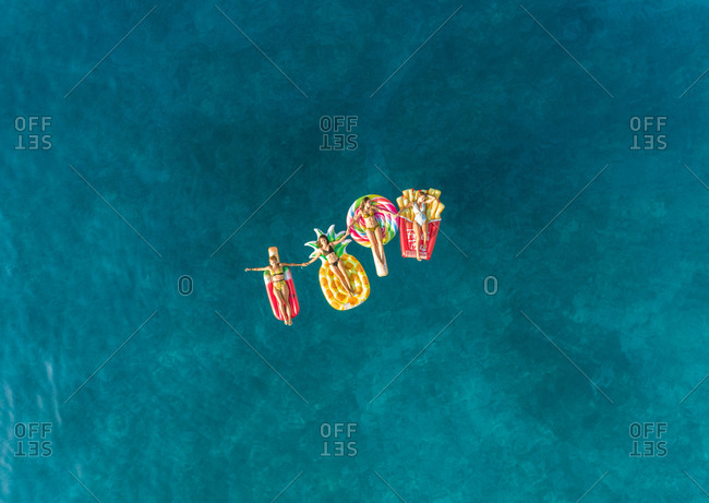 Aerial view of four women friends posing on floating inflatable mattresses on Atokos island, Greece.