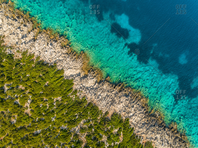 Aerial view of rocky shore and transparent sea off Ithaki, Greece.