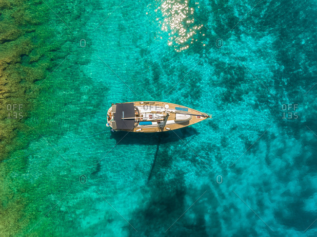Aerial view of one sailing boat anchored on transparent coast, Ithaki, Greece.