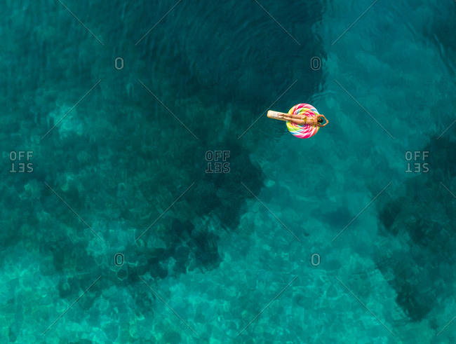 Aerial view of woman floating on inflatable lollipop mattress on Atokos island, Greece.