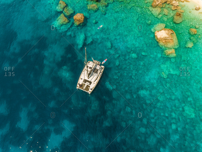 Aerial view of sailboat anchored close to the shore in the mediterranean sea, Sivota Greece.