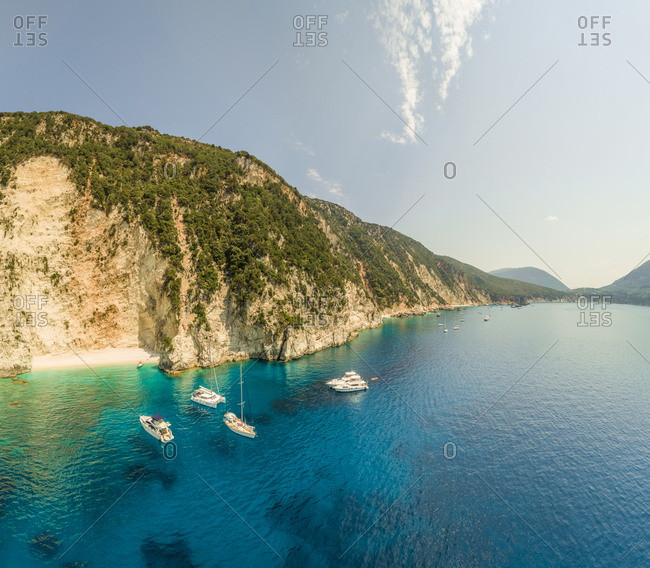 Aerial view group of boats anchored in rocky bay off the coast in Sivota, Greece.