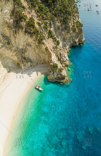Aerial view of boat anchored on beach in Sivota, Greece.