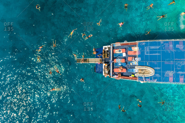 Aerial view of people swimming and diving off ferry, Ithaki island, Greece.