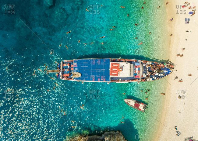 Aerial view of people disembarking off ferry onto sandy beach, Ithaki island, Greece.