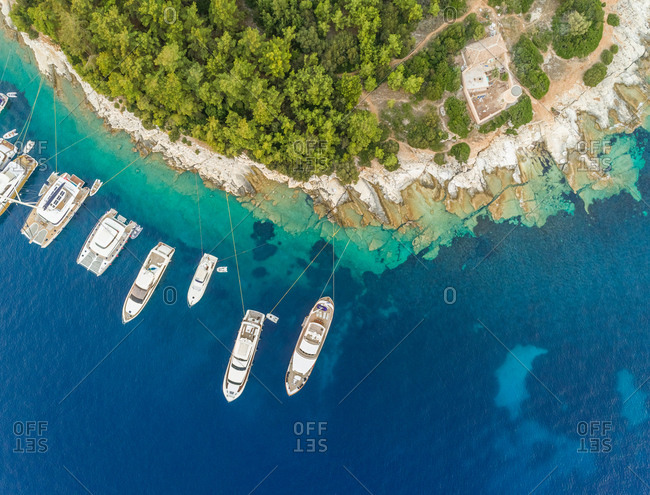 Aerial view above of group of boats anchored on the shore of Kefallonia, Greece.
