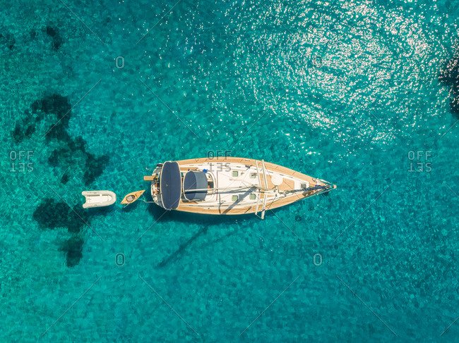 Aerial view of sailboat anchored in crystal water on mediterranean sea, Varko, Greece.