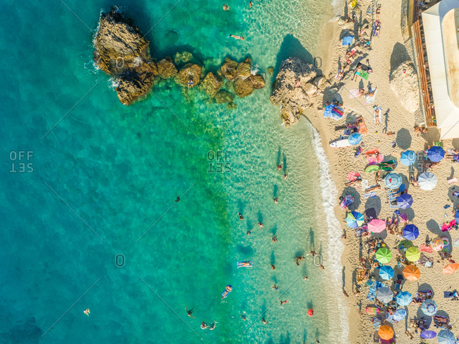 Aerial view of crowded beach with vacationers and parasols, Lefkada, Greece.
