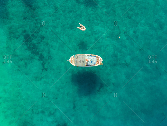 Aerial view of small fishing boat anchored on the coast of Agios Nikitas, Greece.