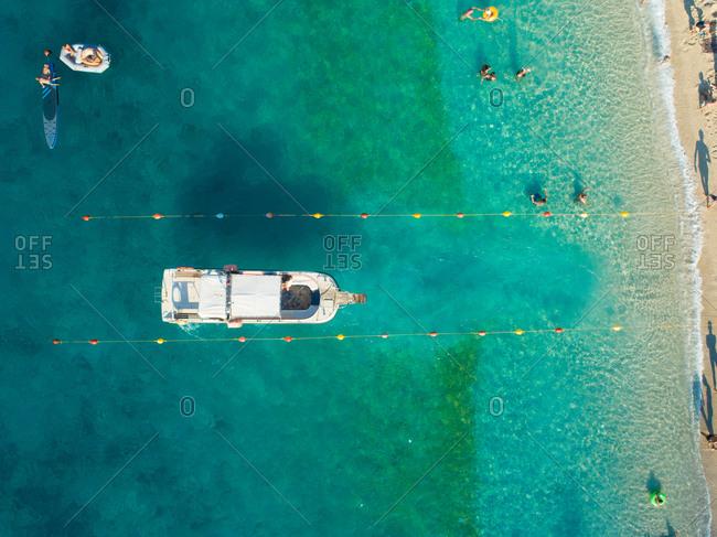 Aerial view of passenger boat entering buoy line on beach coast of Agios Nikitas, Greece.
