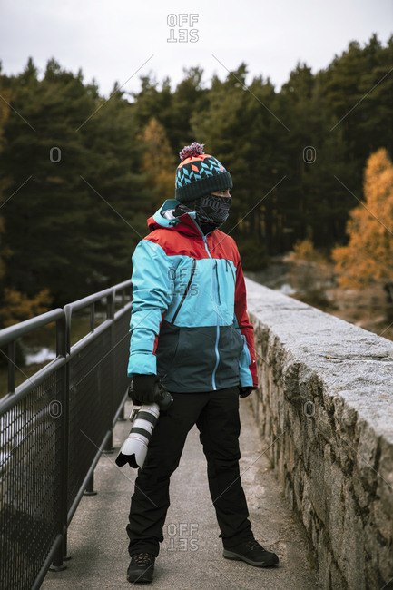 Man standing on bridge with camera in late fall