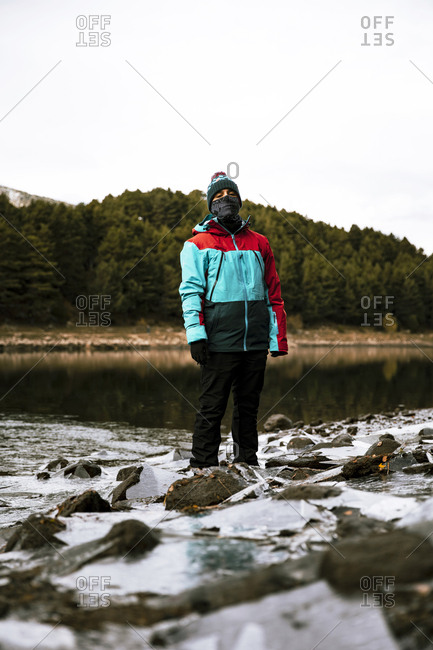 Man standing in river in late fall