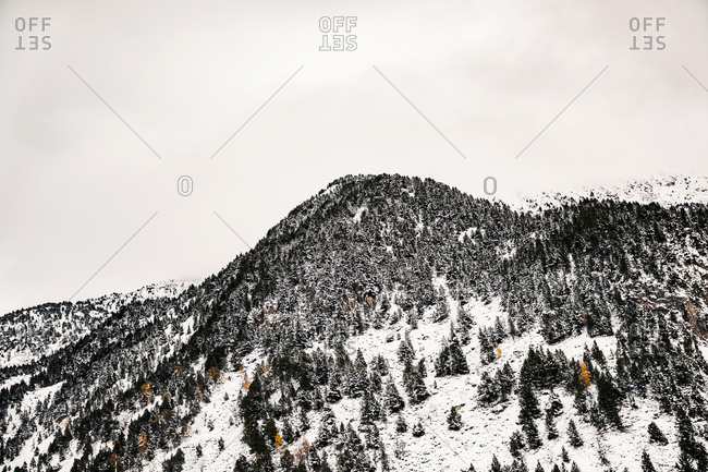 Clouds over snowy mountains and trees in late fall