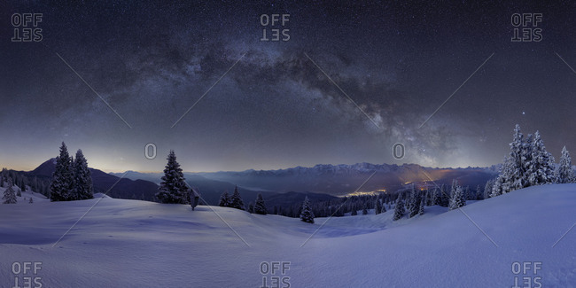 Milky way above the Karwendel, in the foreground the snowy alpine meadow of the Wallgau Alm with powder snow on the trees, the illuminated places are Kryn and Mittenwald, mountains: Simetsberg, Benediktenwand, Karwendel mountains, Arnspitze