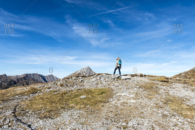 Woman with backpack wandering over a ridge, Hahntennjoch, Tyrol, Austria, Europe