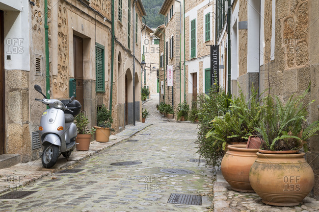 March 2, 2018: Parked scooter and potted plants in an alley in Fornalutx, Mallorca, Balearic Islands, Spain