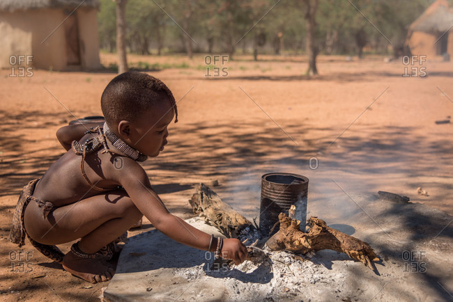 April 20, 2017: Himba girl makes fire in a Himba village in Namibia