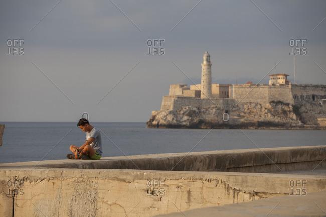 April 18, 2015: Promenade Malecon with fortress Castillo de los Tres Reyes del Morro, Havana, Cuba