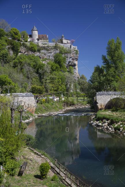 Collapsed old bridge in front of castle rock near Vitrac, Dordogne, France