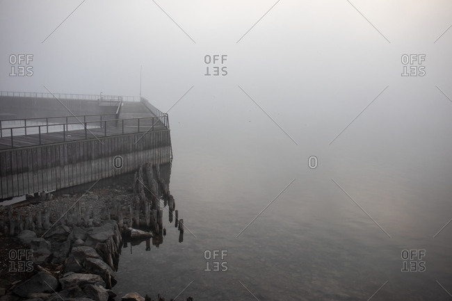 Wooden pier by the ocean on a foggy day