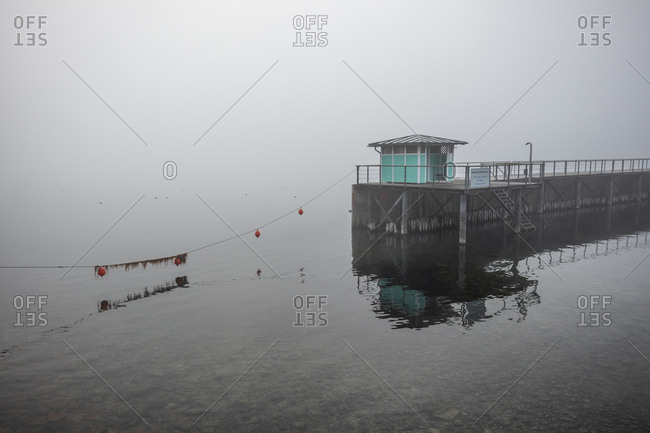 Floats and building at the end of a pier on a foggy day