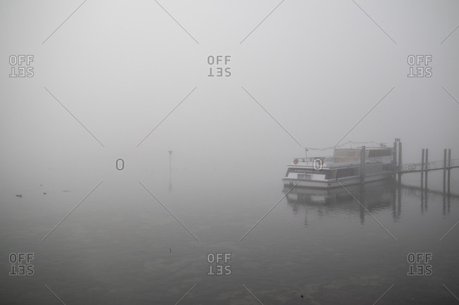 November 25, 2018: Boat moored at a dock in dense fog