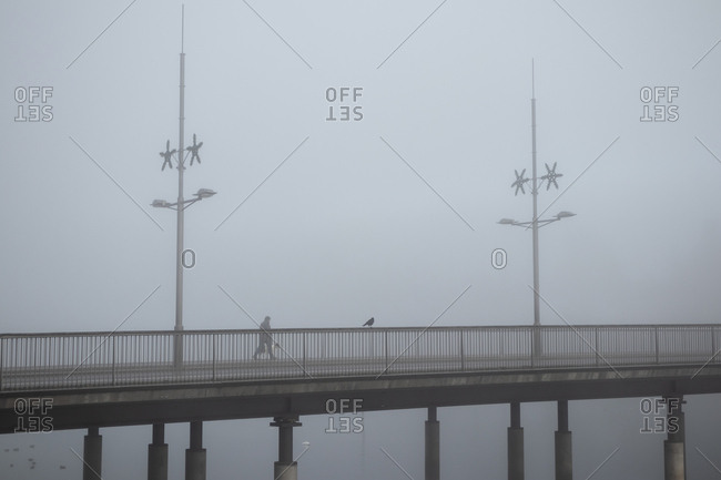 Person walking across bridge on a foggy day