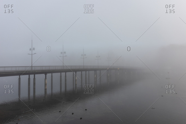 Pier over the ocean in dense fog