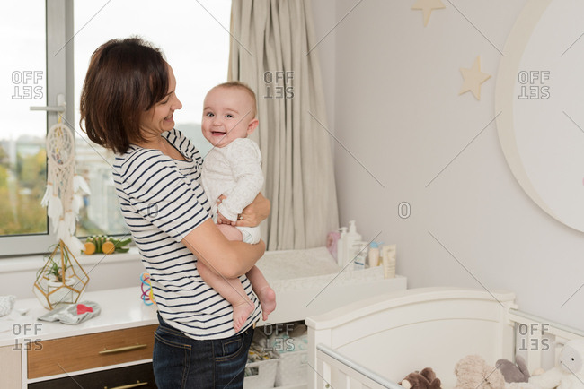 Mother with baby boy in arms standing in nursery