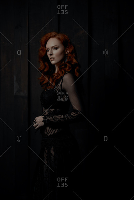 Young woman with long, curly red hair wearing black lace dress