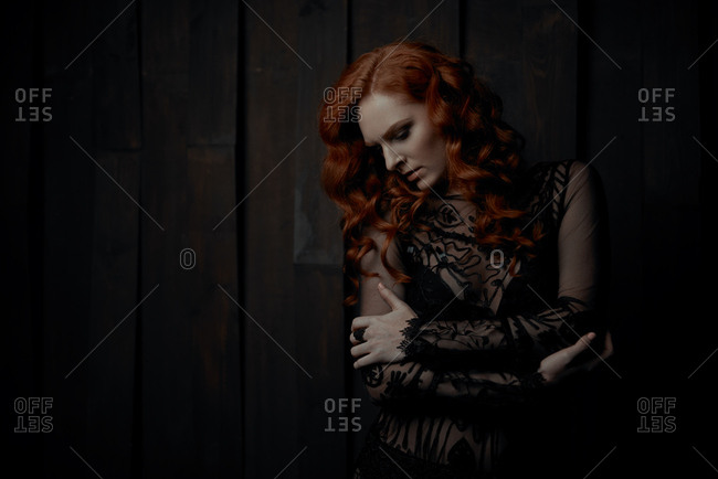 Portrait of a young woman with long, curly red hair wearing black lace dress