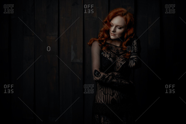 4df89b2e1f Portrait of a red haired young woman wearing black lace dress stock photo -  OFFSET