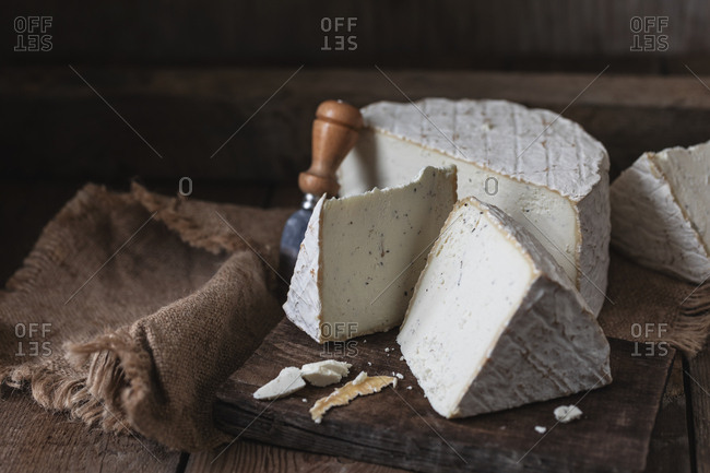 homemade cheese over on old wooden table. rustic background dark moody photo