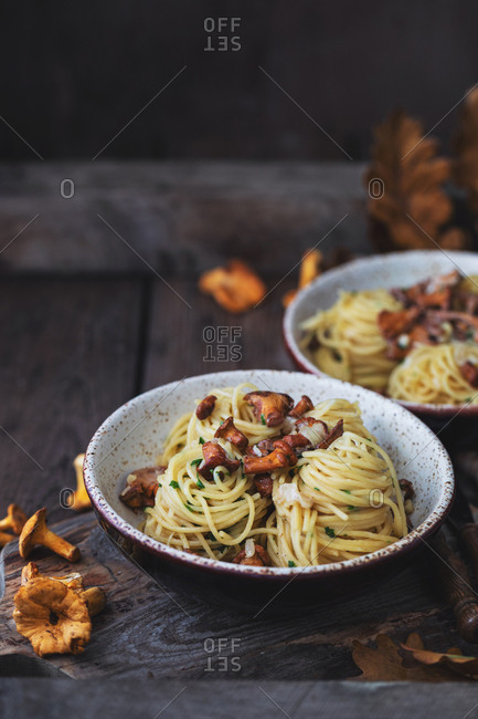Pasta with freshly picked chanterelle mushrooms, cheese and herbs on old wooden table