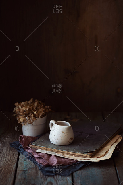 still-life milk jug near a cup of dried flowers and old book over wooden table
