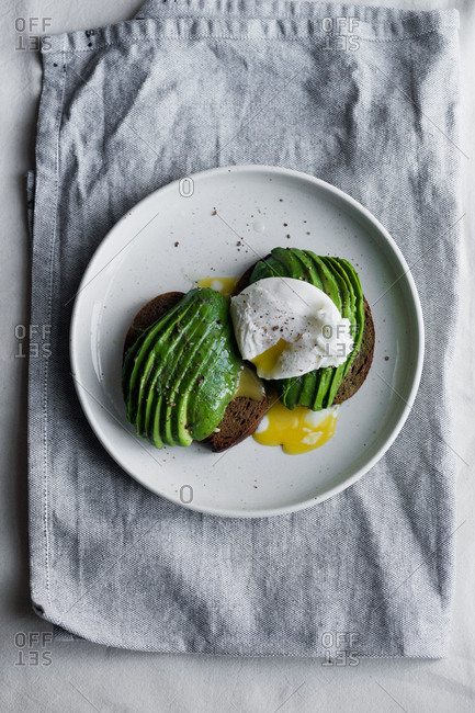 Avocado sandwich on rye toasted bread with poached egg
